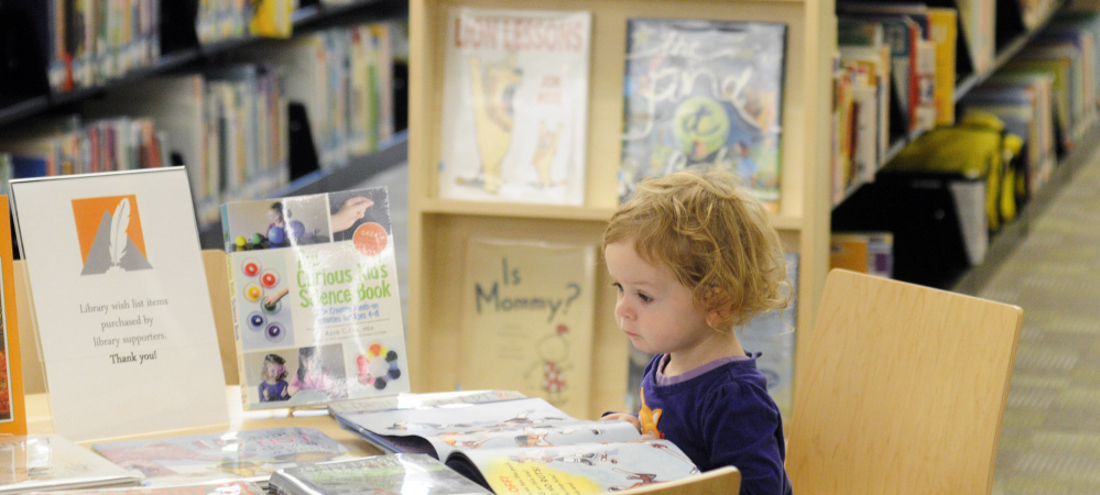 Mari Voorhies looks at books in the children's room Saturday at the reopened Lithgow Public Library in Augusta.