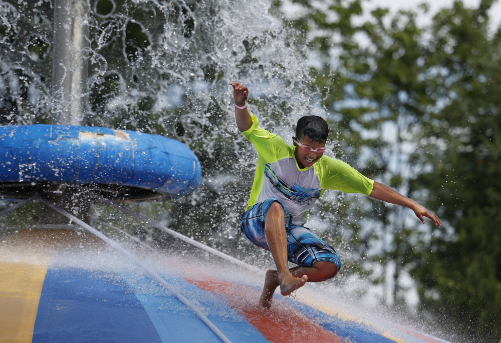 J.J. Camacho, 9, of New York City enjoys the Aquasaucer slide during a gathering of Fresh Air Fund kids and families at Aquaboggan Water Park in Saco on Sunday.