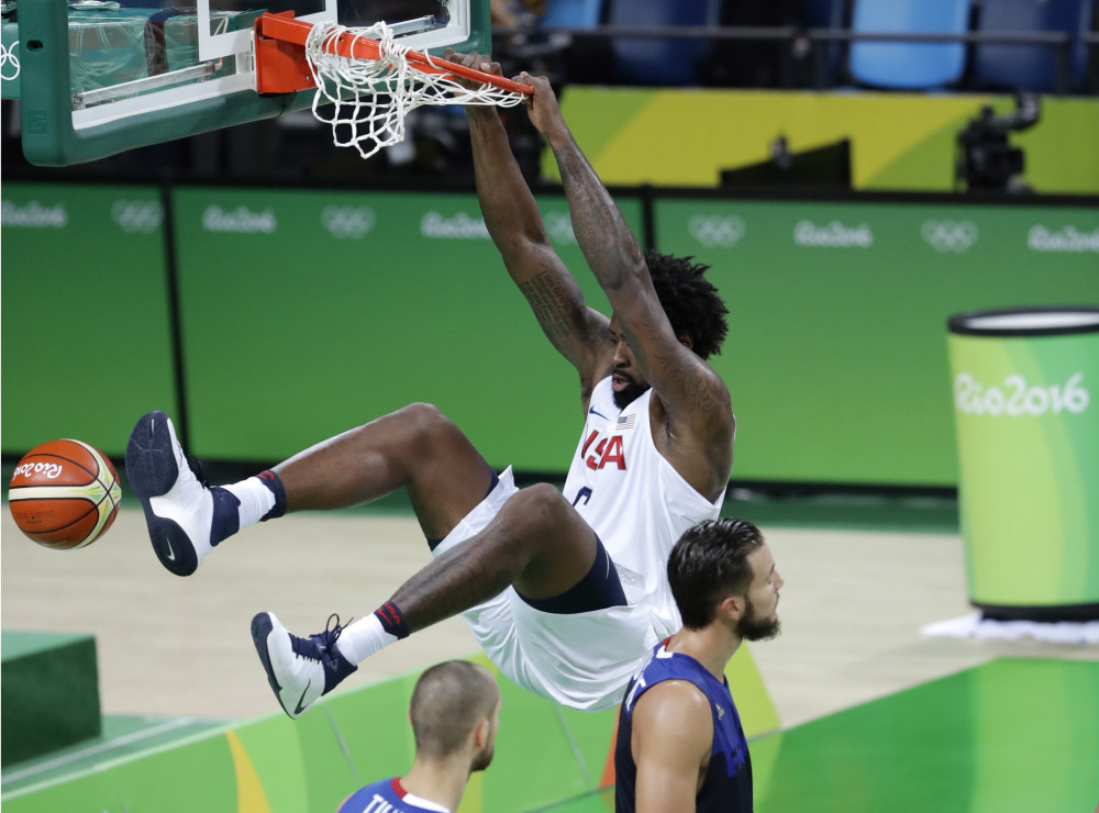 United States' DeAndre Jordan hangs on the rim as he scores against France during Sunday's game at the 2016 Summer Olympics in Rio de Janeiro.