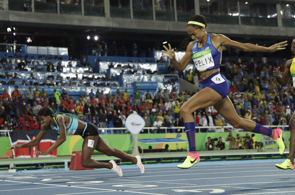 Bahamas' Shaunae Miller falls over the finish line to win gold ahead of United States' Allyson Felix, right, in the women's 400-meter final Monday night in Rio de Janeiro.