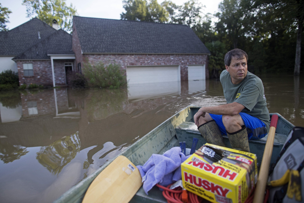 David Key boats away from his flooded home after reviewing the damage in Prairieville, La., Tuesday, Aug. 16, 2016. Key, an insurance adjuster, fled his home as the flood water was rising with his wife and three children and returned today to assess the damage. (