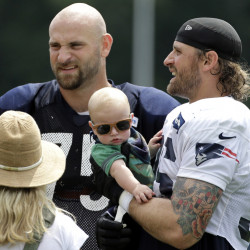 Defensive end Chris Long of the Patriots, right, holds his 5- month-old son, Waylon, while meeting his brother Kyle, a Bears offensive lineman. The teams are working out together.