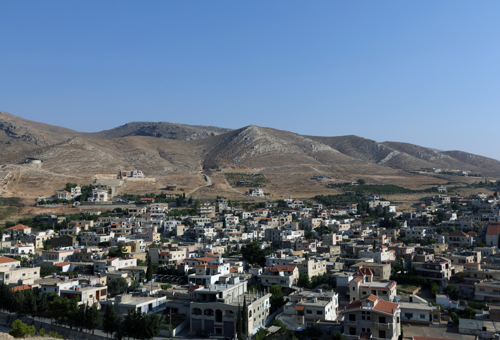 This Wednesday, Aug. 13, 2014 photo, shows a general view of Lebanon's Ras Baalbek, a Christian town in the northern Bekaa region near the border with Syria. Across the Middle East, Christian communities as old as the religion itself feel their very survival is at stake, threatened by militants of the Islamic State group rampaging across Iraq and Syria. Many Christian villagers are setting up self-defense units to protect themselves against attack. In Qaa and Ras Baalbek, two Christian northeastern villages on the border with Syria, many of the thousands of expatriates who used to spend the summer there stayed away this year. (AP Photo/Bilal Hussein)