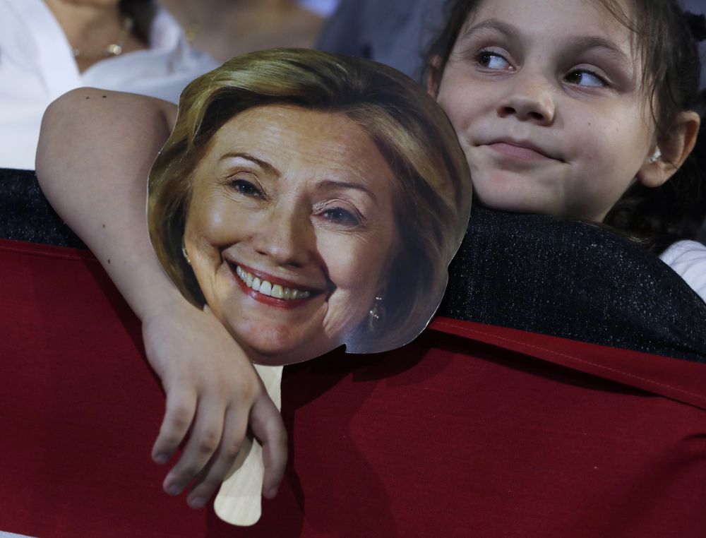 Hunter Lassus, 7, of Seven Hills, Ohio, holds an image of Democratic presidential nominee Hillary Clinton during a campaign event in Cleveland on Wednesday.