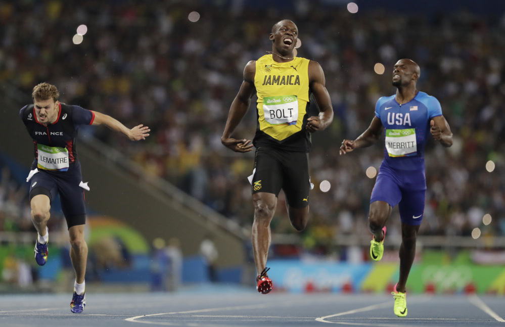 Usain Bolt of Jamaica, center, celebrates after crossing the line to win the gold medal in the men's 200-meter final Thursday in Rio de Janeiro, Brazil.