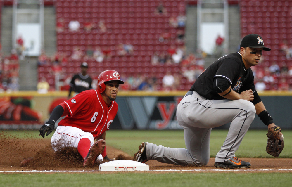 Cincinnati Reds' Billy Hamilton, left, slides into third with a steal as the ball gets away from Miami Marlins third baseman Martin Prado during the thrid inning of a baseball game Thursday, Aug. 18, 2016, in Cincinnati. (AP Photo/Gary Landers)