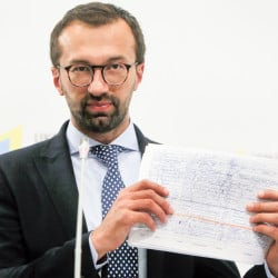 Serhiy Leshchenko, a former investigative journalist turned lawmaker, shows a copy one of the once-secret accounting documents of Ukraine's pro-Kremlin party that were released  and purporting to show payments of $12.7 million earmarked for Donald Trump's campaign chairman Paul Manafort, during a news conference in Kiev, Ukraine, on Friday.