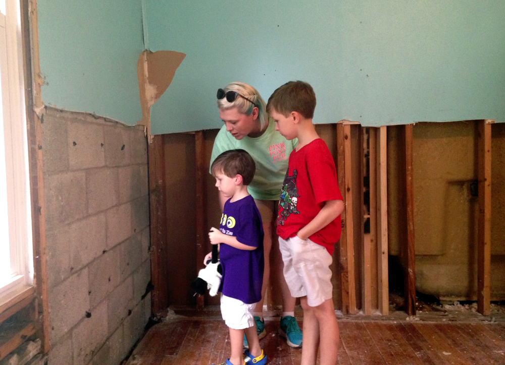 """Amanda Burge, 35, looks at flood damage with her sons Aiden, right, and Hudson at their home in Denham Springs, La., Friday. """"Everything is gone,"""" she said."""