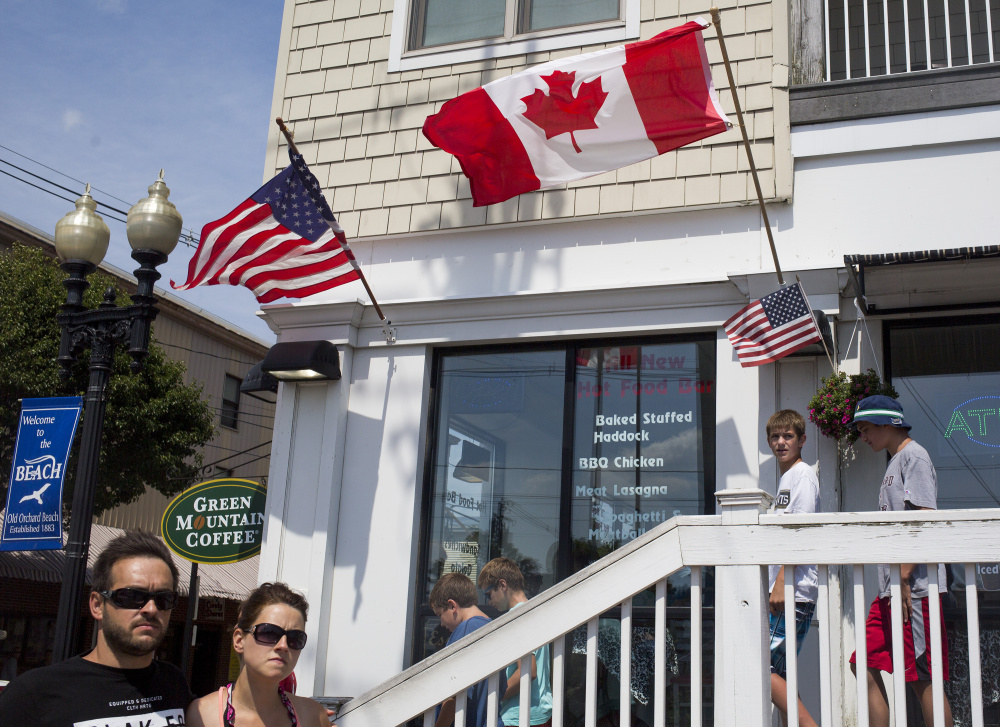 Canadian and American flags wave recently outside a restaurant in Old Orchard Beach. This coastal Maine town has long been a preferred destination for Canadian tourists, especially from Quebec.
