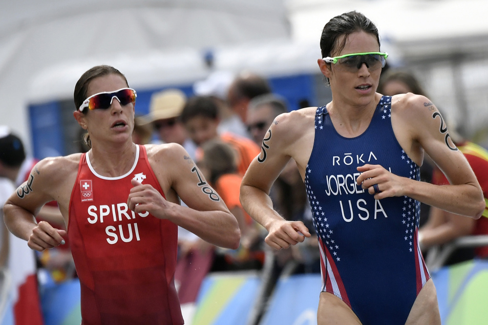 Gwen Jorgensen, right, of the U.S. and defending Olympic champion Nicola Spirig of Switzerland run side-by-side during Saturday's triathlon. Jorgensen pulled away in the final mile to win the gold medal.