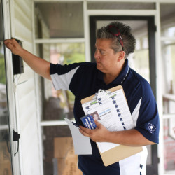 Crystal Moore knocks on a door as she campaigns door-to-door, in Latta, S.C. She has set her sights on becoming the state's first elected female and openly gay sheriff.