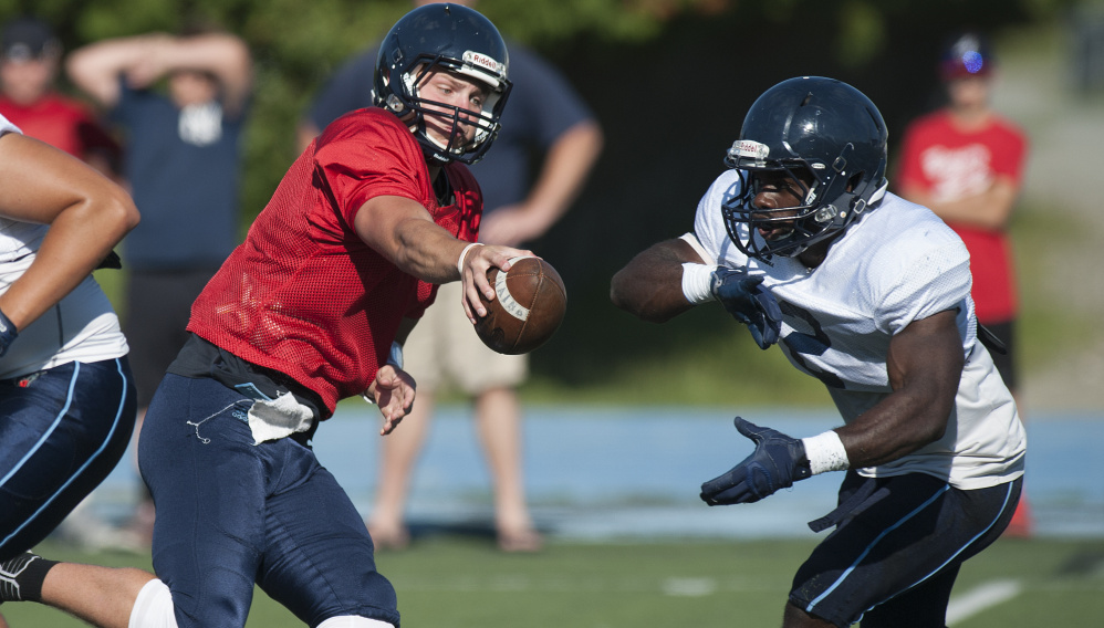 Maine quarterback Dan Collins fakes a handoff to Nigel Beckford during the Black Bears' final scrimmage Sunday in Orono. Collins threw three touchdowns.