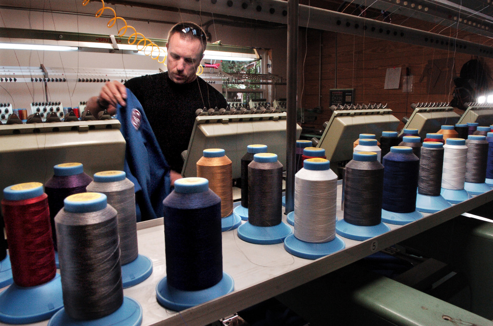 OriginUSA employee Peter White prepares to embroider a gi garment at the company manufacturing facility in Industry.