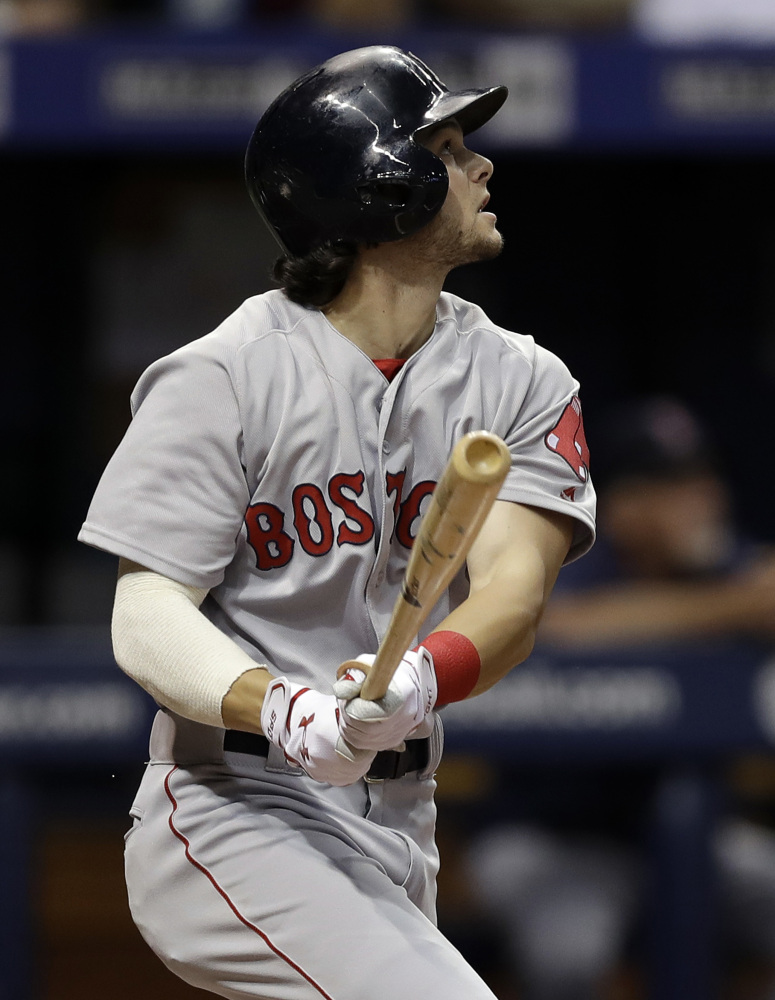 Boston's Andrew Benintendi hits a sacrifice fly off Tampa Bay pitcher Blake Snell, driving in Sandy Leon in the fourth inning of Monday night's win in St. Petersburg, Fla. In the eighth inning, Benintendi made a spectacular catch to rob Steven Souza Jr. of a two-run home run.