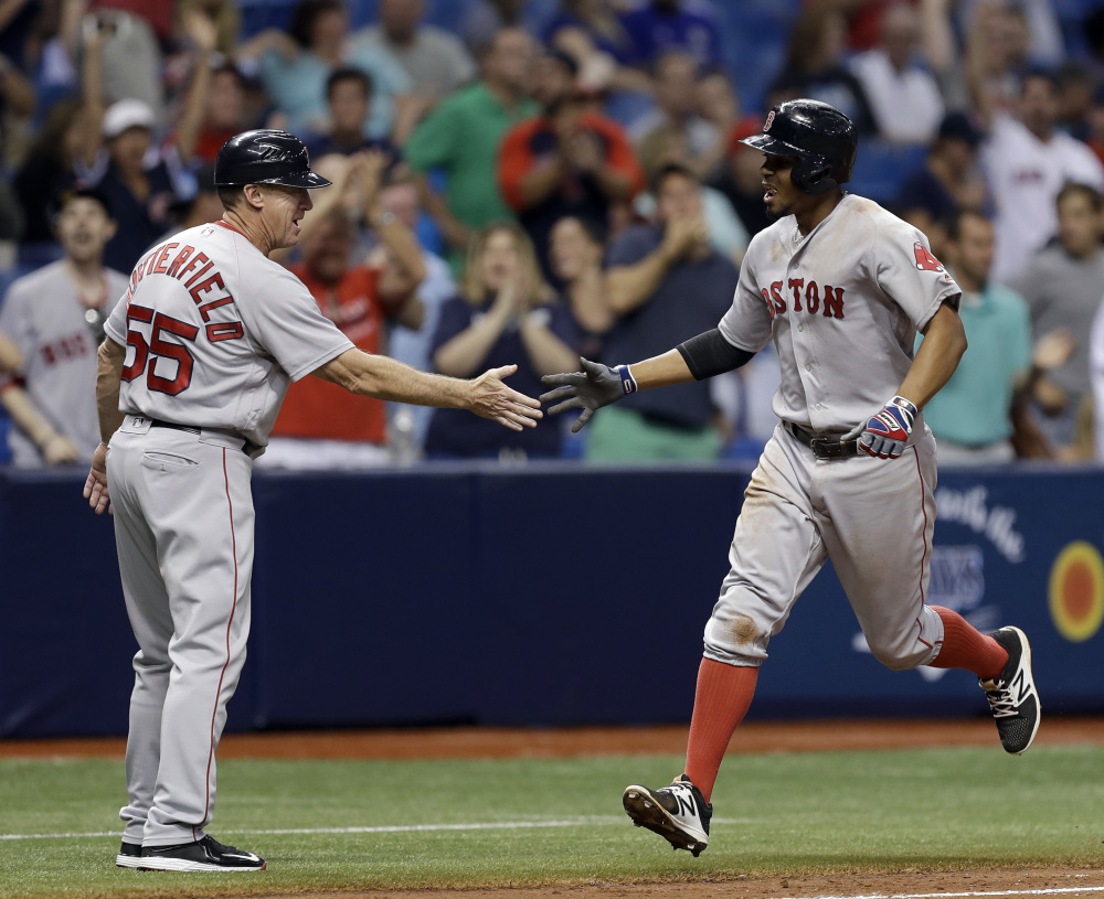 Xander Bogaerts shakes hands with third base coach Brian Butterfield after hitting a two-run home run in the ninth inning Monday night.