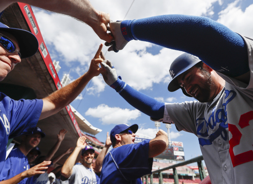 The Dodgers' Adrian Gonzalez, right, celebrates in the dugout after hitting a three-run home run off Reds relief pitcher Jumbo Diaz in the seventh inning of an 18-9 win at Cincinnati on Monday. Gonzalez hit three home runs in the game, driving in a career-high eight runs.