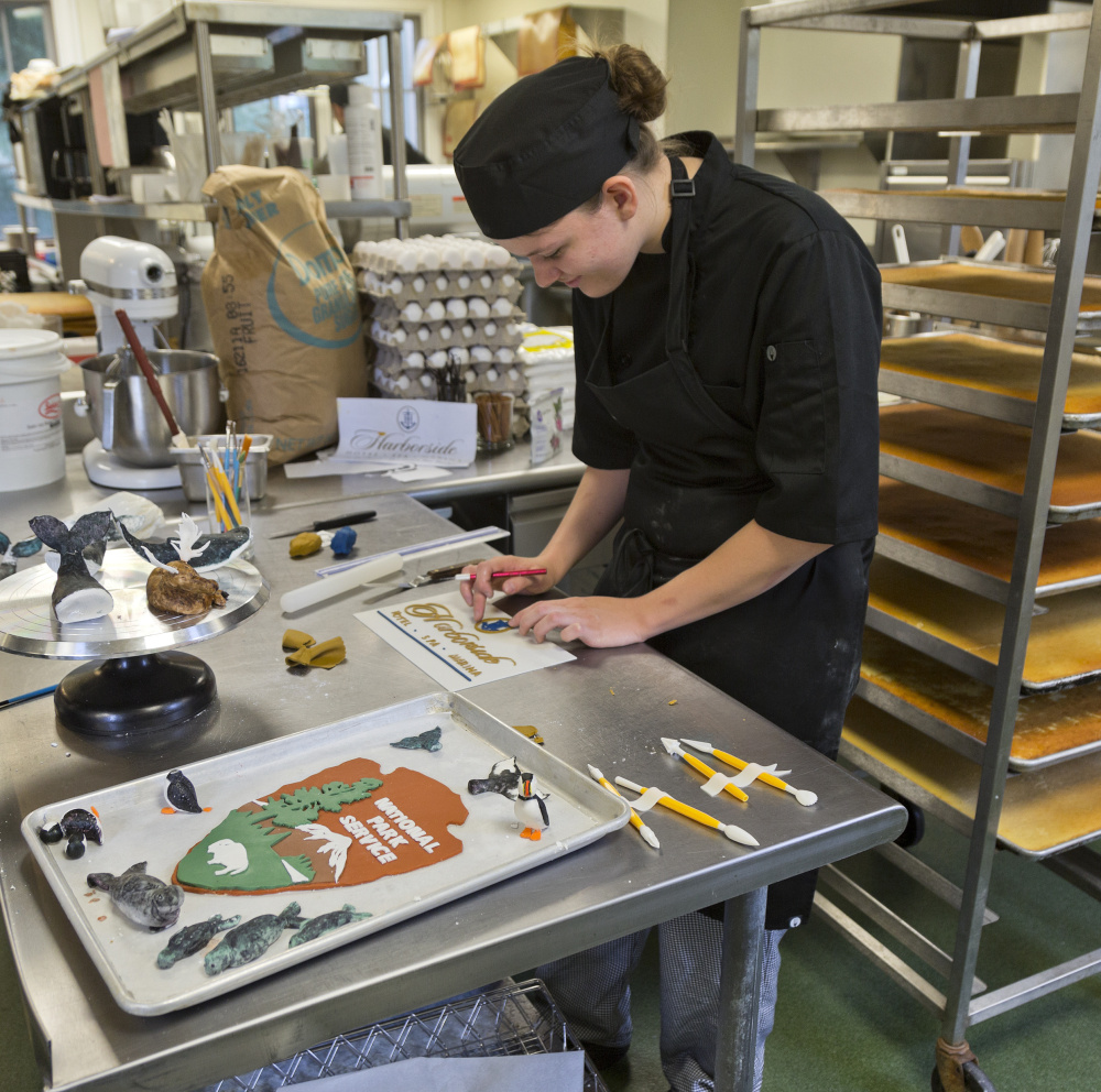 A chef works on details for a giant cake celebrating Acadia National Park's 100th anniversary. Photo by Mike Perlman