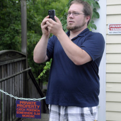 Stephen Turcotte plays Pokémon Go on Monday between signs on a stairwell in Hallowell that indicate the property is private.