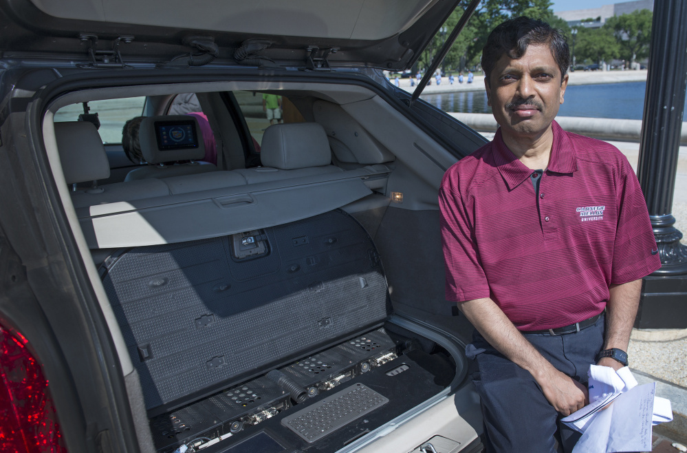 Carnegie Mellon University Professor Raj Rajkumar, shown in 2014 with the main control center of a self-driven car, said he is more convinced than ever that gradually introducing safe-driving features such as lane-departure warnings, cameras and sensors is the prudent path. At left, Google's self-driving Lexus motors  along a street during a demonstration at Google campus in Mountain View, Calif.