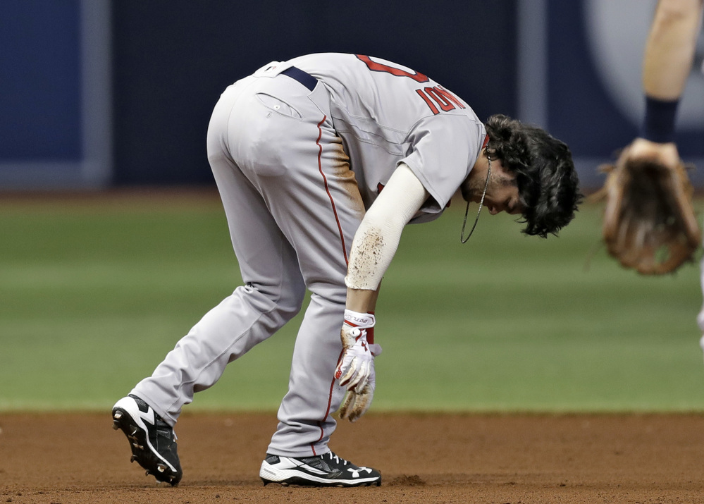 Boston's Andrew Benintendi tries to get to his feet after injuring his leg in a double play in the seventh inning Wednesday night in St. Petersburg, Fla. Benintendi left the game.