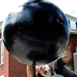 """Sculptor Jay Sawyer, shown Thursday, gets under his sculpture """"F Bomb,"""" part of his exhibit at the Emery Community Art Center at the University of Maine in Farmington on. Saywer's exhibit, """"Sculpture Soup,"""" uses letters of the alphabet to create wordplay."""