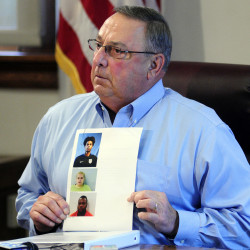 Gov. Paul LePage holds up booking mug shots from a three-ring binder of news releases and articles about drug arrests during a meeting with reporters on Aug. 26, 2016, in the State House Cabinet room in Augusta.Photo by Joe Phelan/Kennebec Journal