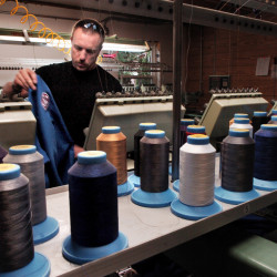 OriginUSA employee Peter White prepares to embroider a martial arts garment at the company's manufacturing facility in Industry. Origin USA has started to make the fabric it uses in the manufacture of jiu jitsu gis, the uniforms worn by practitioners of certain martial arts. The 4-year-old company now employs 20 and produces 60 units a day at its factory in Industry. The company recently added several product lines ranging from apparel to training equipment and backpacks.  David Leaming/Morning Sentinel