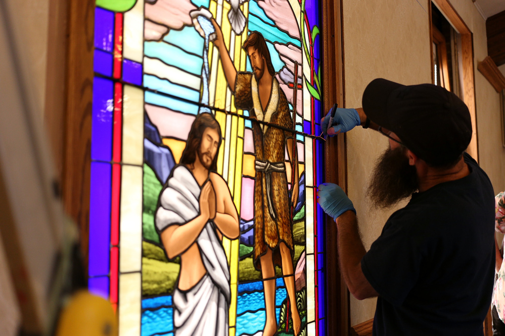 Ruben Llano works on the installation of a handmade glass window Thursday at the Addison Congregational Church in Addison Mich.
