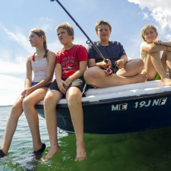 Young campers fish from the bow of a boat tied to the pier at Warren Island State Park. From left are Ella Villeneuve, Kelvy Hunter, Connor Bickford and Nora Villeneuve.
