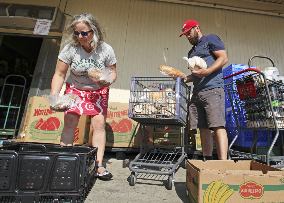 Katie Brown, executive director of The Locker Project, and volunteer Stephen Davis Phillips load boxes of produce and bread that will be donated to local schools as part of the two-year-old Locker Project.