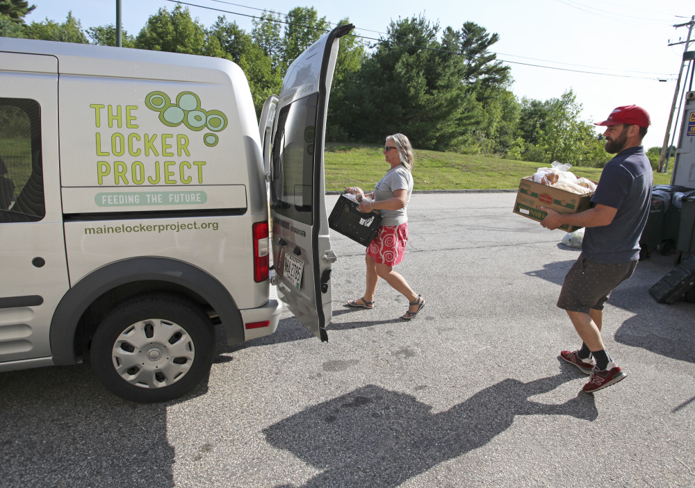 Katie Brown, executive director of The Locker Project, and volunteer Stephen Davis Phillips load boxes of food into the organization's van Wednesday. Jill Brady/Staff Photographer