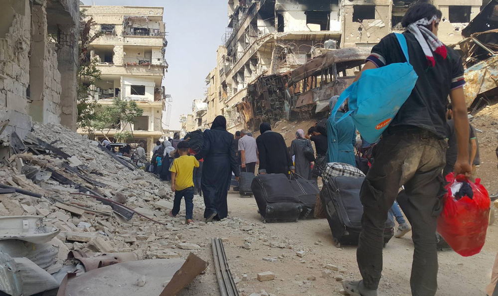 Syrian citizens carry their belongings as they prepare to evacuate from Darayya, a blockaded Damascus suburb, on Friday under a deal struck between the rebels and the government.
