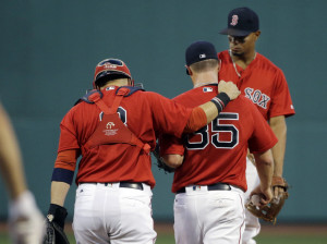 Red Sox catcher Sandy Leon puts his arm around starting pitcher Steven Wright as shortstop Xander Bogaerts approaches for a mound conference in the first inning Friday night against the Kansas City Royals at Fenway Park. Wright gave up five runs in the first inning.