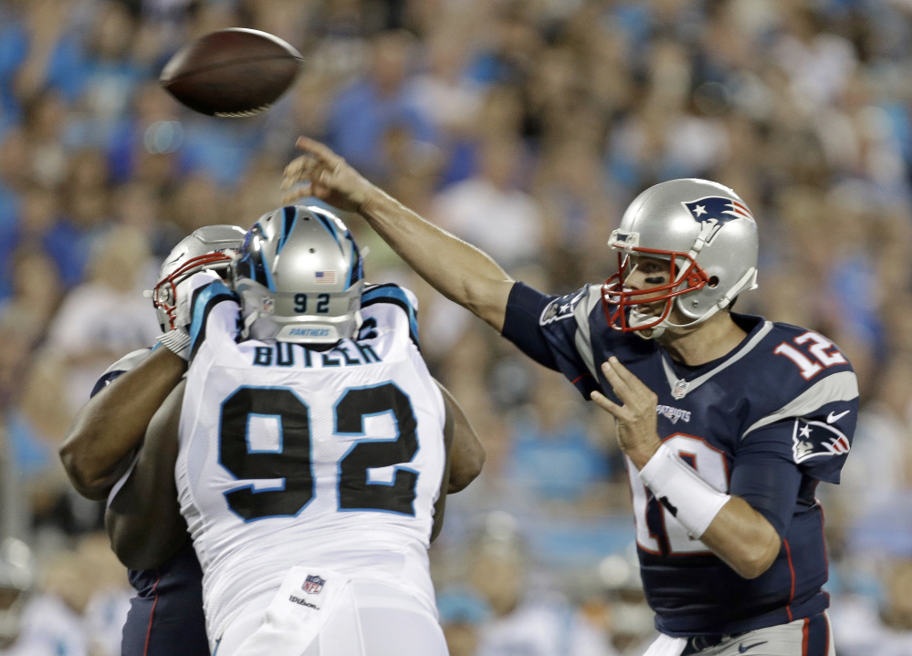 Patriots QB Tom Brady throws a pass under pressure from Carolina's Vernon Butler in the first half Friday night at Charlotte, N.C.