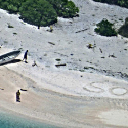"Two stranded mariners signal for help with an ""SOS"" in the sand as a Navy P-8A Poseidon aircraft crew flies over as part of a Coast Guard search of the Pacific on Wednesday."