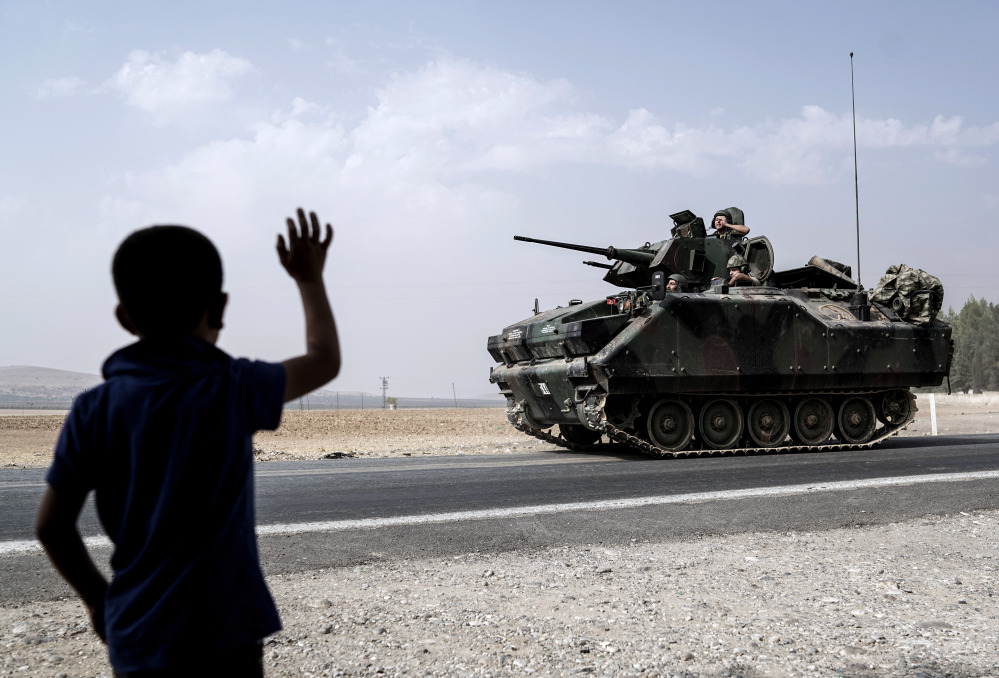 A child waves at Turkish troops heading to the Syrian border, in Karkamis, Turkey, on Friday. Turkish tanks led the assault last week that recaptured Jarabulus, Syria, from Islamic State militants in a relatively bloodless victory.