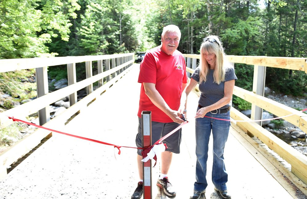 Ralph Luce, president of the North Franklin Snowmobile Club, cuts a ribbon with volunteer Nancy Perlson on Saturday during a ceremony marking the opening of the Perham Stream Bridge in Madrid Township.