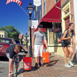From left, Phillip Jones, Luke Robinson and Clarrissa Lettre pick up cigarette butts and other trash Saturday as they play Pokemon Go on Water Street in Hallowell.
