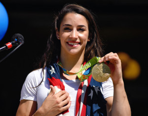 Aly Raisman shows off her gold medal at the Rally for Aly in Needham, Mass., on Saturday.