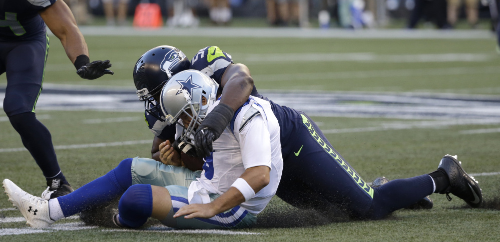 Cowboys quarterback Tony Romo is tackled by Seattle defensive end Cliff Avril in a preseason game on Thursday. Romo suffered a broken bone in his back on the play.