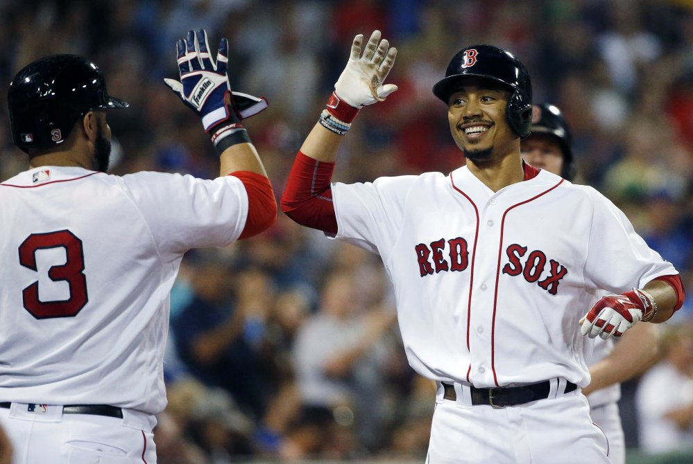 Mookie Betts, right, celebrates with Sandy Leon after hitting a home run in the fifth inning Saturday night – one of three homers for the Red Sox in an 8-3 win over the Kansas City Royals.