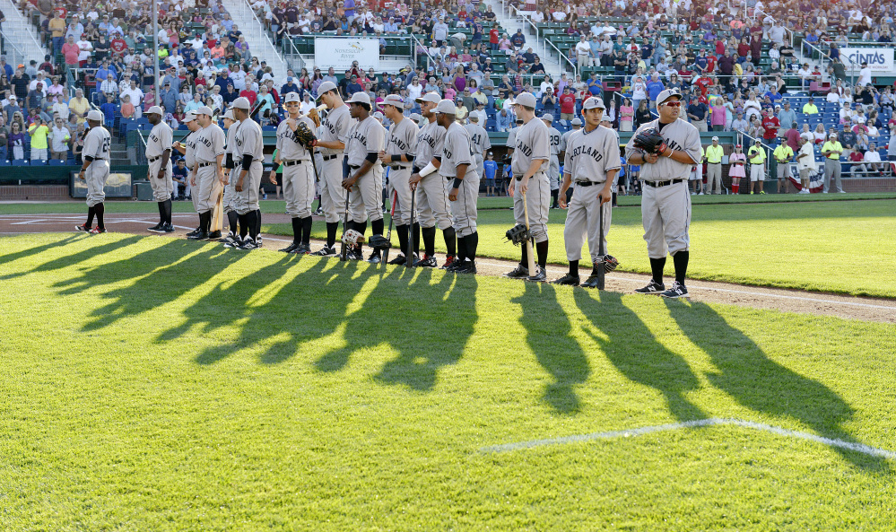 Portland Sea Dogs players, wearing throwback uniforms from the Portland Eskimos of the 1920s, line up along the first-base line on