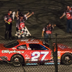 Wayne Helliwell Jr.'s pit crew celebrates as Helliwell waves the checkered flag during his victory lap after winning the Oxford 250 on Sunday night at Oxford Plains Speedway. Ben McCanna/Staff Photographer