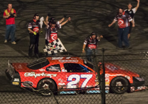 Ben McCanna/Staff Photographer Wayne Helliwell Jr.'s pit crew celebrates as Helliwell waves the checkered flag during his victory lap after winning the Oxford 250 on Sunday night at Oxford Plains Speedway.