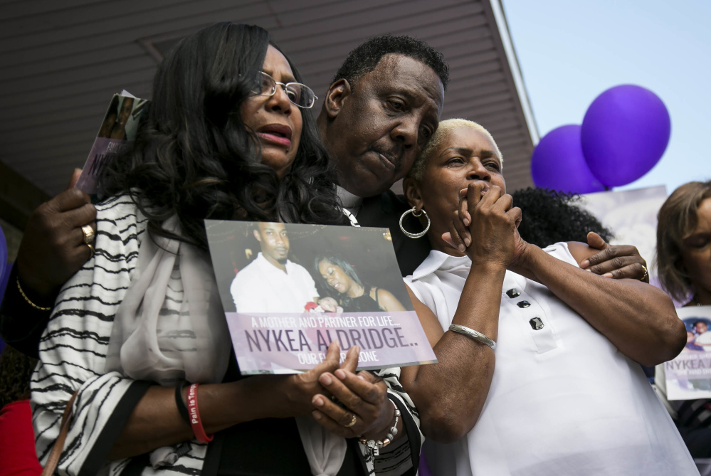Family members and supporters hug Diann Aldridge, left, during a vigil for her daughter Nykea Aldridge on Sunday. There were 65 homicides in July alone in Chicago.