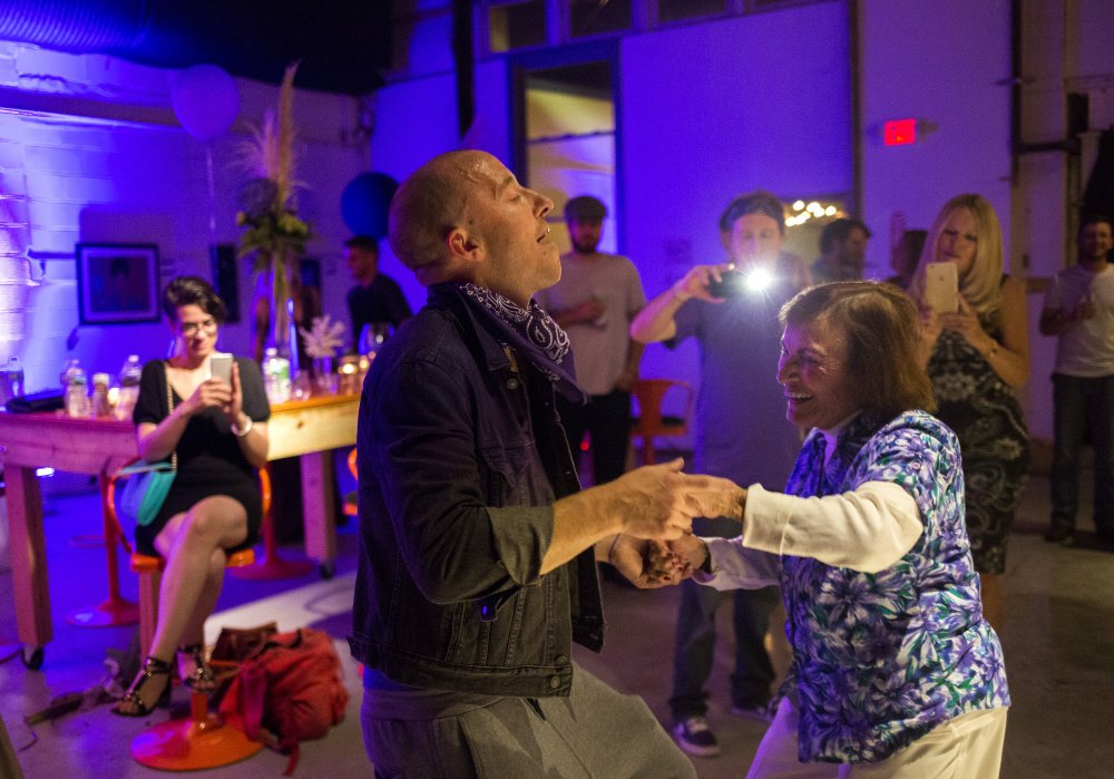 At his bathed-in-purple birthday party, Sam Koenigsberg dances with his grandmother Jaqueline McLain.