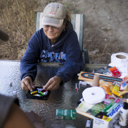 Homeless people play a board game Monday under a turnpike overpass where they have set up tents and hope to remain. Brianna Soukup/Staff Photographer