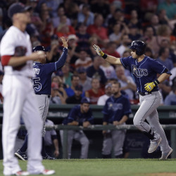 Tampa Bay's' Evan Longoria  is congratulated by third base coach Charlie Montoyo after his solo home run off Red Sox pitcher Clay Buchholz during the eighth inning.   Associated Press/Charles Krupa