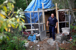 Community Policing Sgt. Andrew Hutchings makes rounds at the homeless encampment behind the Pine Tree Shopping Center on Wednesday, checking cabins and tents for residents. Police were there to let any residents remaining know that they have to be gone by Thursday.