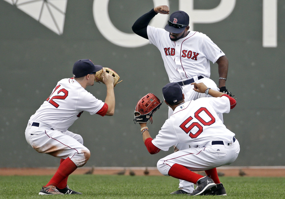 Red Sox outfielders Brock Holt, left, Mookie Betts, right, and Jackie Bradley Jr. celebrate after the win over Tampa Bay. Bradley had three hits, including a home run.